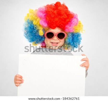 Happy child with clown wig holding the blank paper