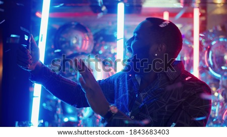 Portrait of smiling male person doing selfie photo on neon lamps background. Closeup afro man showing victory sign under confetti in slow motion. African american man making photos at night club party