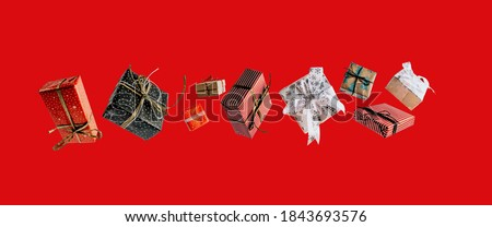 Christmas gift boxes falling or flying in motion on red background. Christmas shopping concept. Royalty-Free Stock Photo #1843693576