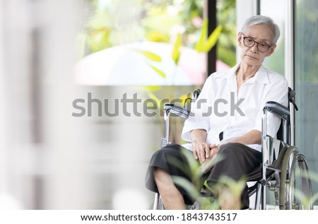 Sad and depressed asian senior woman sitting alone in wheelchair with head down feel lonely and bored,disabled old elderly with loneliness waiting for her family to come visit her at the nursing home Royalty-Free Stock Photo #1843743517