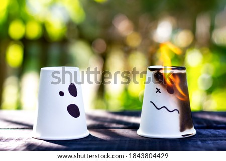 Two cups with a worried expression. One of the cups is on fire. Metaphor of relationships, problems of society. Feelings, emotions