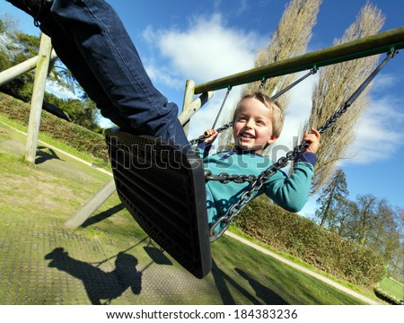 Carefree child on a swing in a park on summer day #184383236