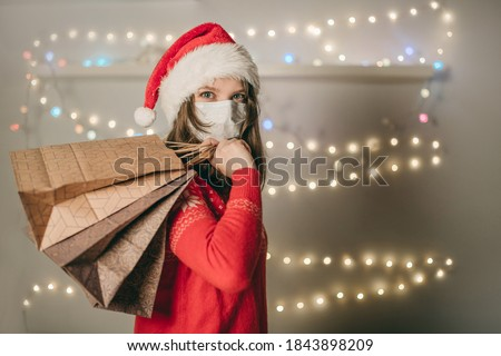 A young European woman in a white medical mask and Christmas red hat walks in the store with gift packages behind her back and bokeh lights, garlands, decoration. Shopping girl, quarantine coronavirus #1843898209