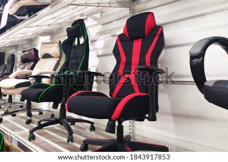 Different computer gamer soft ergonomic chairs in the furniture store #1843917853