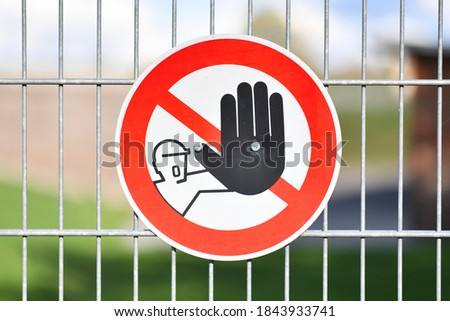 Red round 'Keep out' warning sign with person holding up hand in red circle at fence protecting construction site