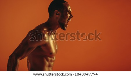 Side view portrait of muscular man shouting aggressively. Cropped shot of bare chested african american man shouting. Royalty-Free Stock Photo #1843949794