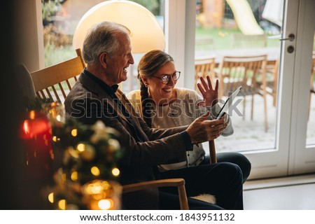 Family having a video call on table pc during christmas. Senior couple greeting family during a video call on a Christmas eve. #1843951132