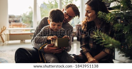 Kid sitting with parents opening gift box while sitting next to christmas tree. Young family celebrating christmas with presents.