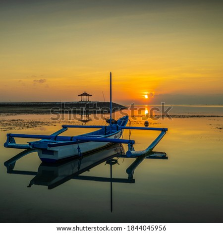 Seascape. Fisherman boat jukung. Sunrise landscape. Gazebos on an artificial island in the ocean. Water reflection. Sun on horizon. Slow shutter speed. Soft focus. Sanur beach, Bali, Indonesia. Royalty-Free Stock Photo #1844045956