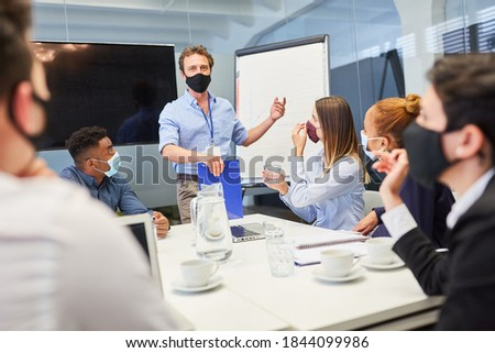 Businessman as a consultant with face mask because of Covid-19 in the consulting workshop Royalty-Free Stock Photo #1844099986