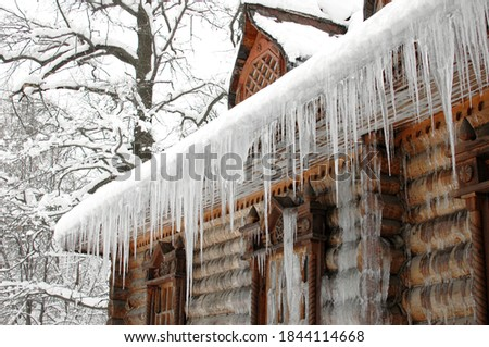 Icicles in winter. The old hut is covered with ice in winter. Icicles hang from the roof. The wooden tower is covered with ice. Icicles hang on the roof of a house. The logs of the hut were frozen Royalty-Free Stock Photo #1844114668
