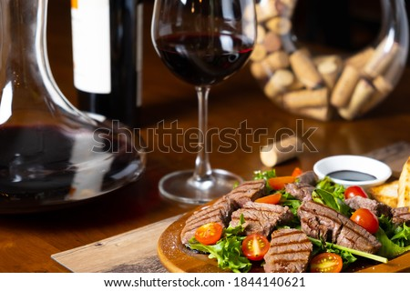 close up of grilled beef tenderloin fillet with rocket salad and cherry tomatoes pairing with Italian fine red wine bottle, glass and decanter in a wooden table classic vintage elegant moody style Royalty-Free Stock Photo #1844140621