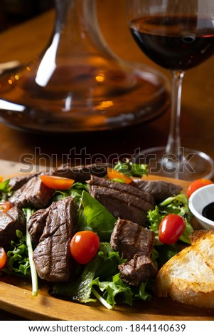 close up of grilled beef tenderloin fillet with rocket salad and cherry tomatoes pairing with Italian fine red wine bottle, glass and decanter in a wooden table classic vintage elegant moody style Royalty-Free Stock Photo #1844140639