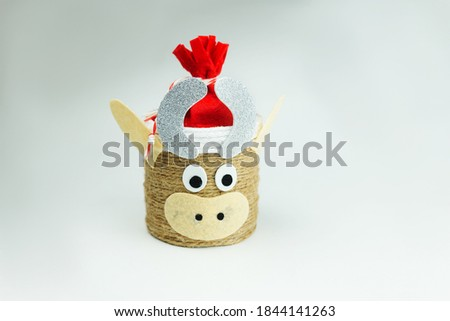 DIY Christmas craft Bull or cow made of jute rope in a red felt hat. Symbol 2021 year