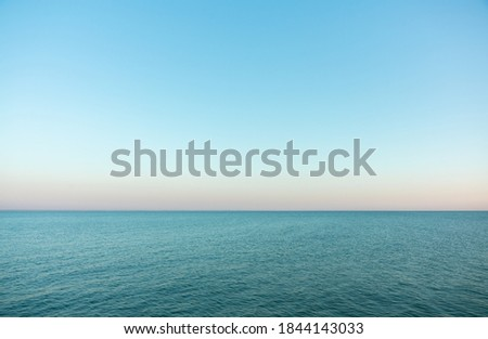 Calm evening sea surface with clear blue sky. Evening seascape.  Royalty-Free Stock Photo #1844143033