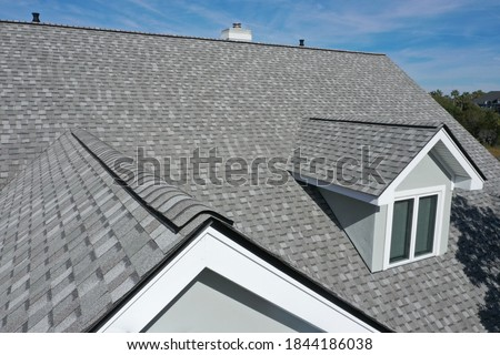 Aerial view of roof work done on a home. Royalty-Free Stock Photo #1844186038
