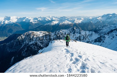Tourist with a backpack and mountain panorama. Climber in a green jacket climbs a mountain against a blue sky. Hiker with backpack standing on top of a mountain and enjoying view. Adventure concept #1844223580