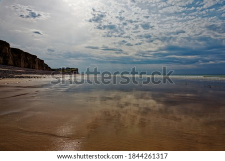 Low tide at sandy beach with rock cliffs. Shining sand surface reflecting cloudy sky. Normandy, France, Europe. Royalty-Free Stock Photo #1844261317