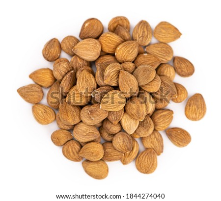 Portion of Apricot Kernels isolated on white background as detailed close up shot (selective focus) Royalty-Free Stock Photo #1844274040
