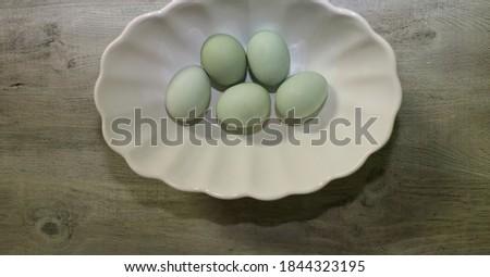 Speckled legbar chicken eggs in al bowl.
