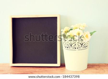 empty blackboard and flowerpot over wooden shelf, retro filter