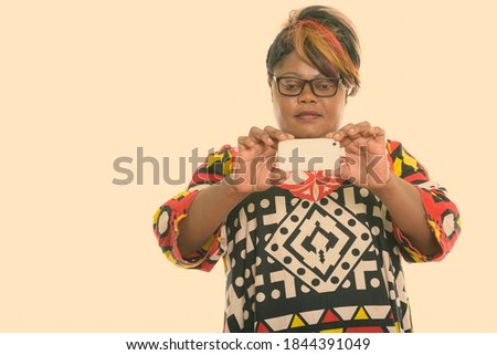 Studio shot of fat black African woman taking picture with mobile phone