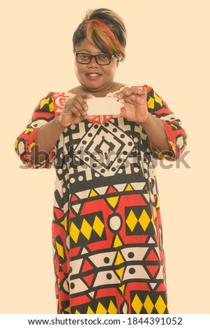 Studio shot of happy fat black African woman smiling and standing while taking picture with mobile phone