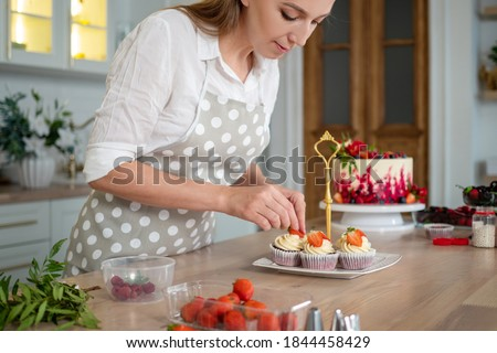 woman in an apron decorates cupcakes with strawberries. pastry chef in the kitchen makes desserts, cakes and muffins. Cooking at home Royalty-Free Stock Photo #1844458429