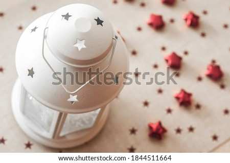 Candlestick in the form of a flashlight with stars and snowflakes on a background of hot stand with stars.