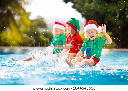 Christmas vacation on tropical island. Kids in Santa hat playing in swimming pool on family Xmas vacation. Winter holidays at the beach. Travel with children. Boy and girl swim. Merry Christmas card. #1844545516