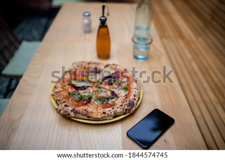 Picture of a tasty looking vegan pizza on a wooden table alongside a bottle of salad dressing, a smartphone, and a blurry glass of mineral water