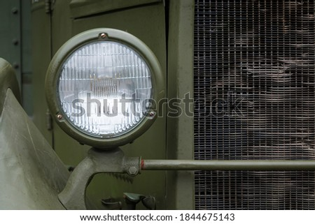 Headlight and a fragment of the cockpit and radiator of an old truck from the Second World War. The casing is painted in a protective green color. Background. Texture. #1844675143