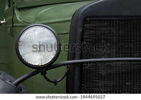 Fragment of the front of a green vintage truck. There is a headlamp with broken glass and part of a radiator. Background. Texture. #1844695027