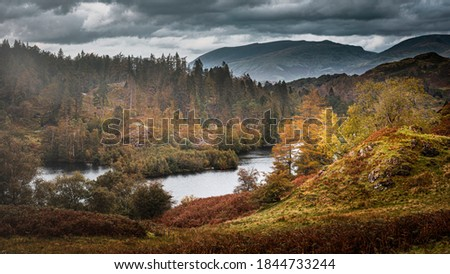 Tarn Hows in autumn.Painterly landscape scene in Lake District, Cumbria,UK.Cloudy sky over scenic mountain valley, lake and hills with trees lit by sunlight.Idyllic scenery. Royalty-Free Stock Photo #1844733244