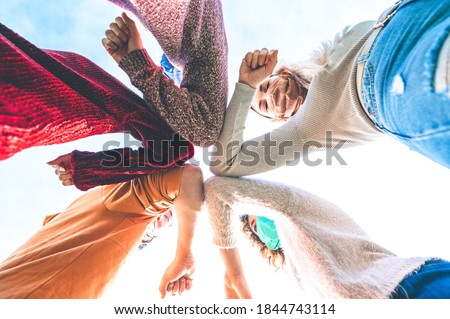 Multiracial young friends bump elbows to say hello in coronavirus time - Concept about avoid the spread of covid-19 - New normal lifestyle concept - Focus on elbow Royalty-Free Stock Photo #1844743114