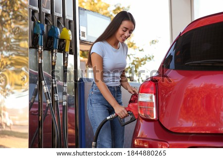 Young woman refueling car at self service gas station Royalty-Free Stock Photo #1844880265