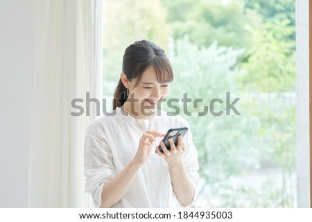 Asian woman using the smart phone at the living room Royalty-Free Stock Photo #1844935003