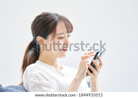 Asian woman using the smart phone on the sofa Royalty-Free Stock Photo #1844935015