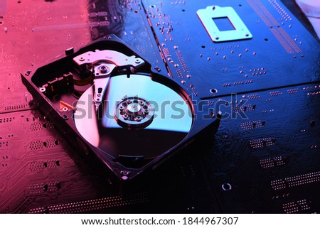 Computer Hard disk drives HDD , SSD on circuit board ,motherboard background. Close-up. With red-blue lighting