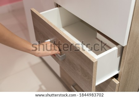 Woman open shelf, pull open drawer wooden in cabinet. Royalty-Free Stock Photo #1844983702