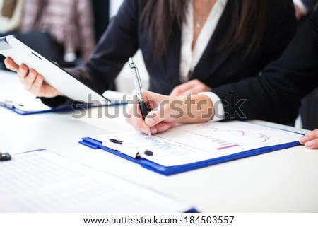 Business people taking notes during a meeting #184503557