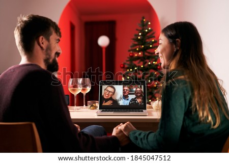 Couple celebrating Christmas in quarantine due to covid 19, making a video call to parents and in-laws. New normal in times of coronavirus. #1845047512