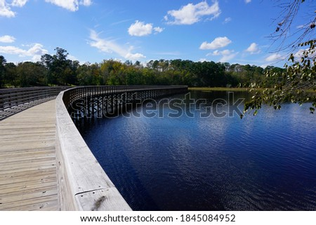Curving boardwalk over Lake Wilson in North Carolina Royalty-Free Stock Photo #1845084952