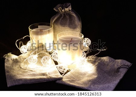 Scented wax candles, three pieces, Christmas garland, composition on a black background, aromatherapy, composition, comfort, atmosphere of comfort and peace #1845126313