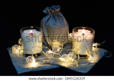 lit scented wax candles, three pieces, Christmas garland, composition on a black background, aromatherapy, composition, comfort, atmosphere of comfort and peace #1845126319