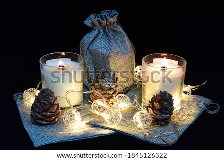 lit scented wax candles, pine cones, Christmas garland, composition, composition on a black background, aromatherapy, composition, comfort, atmosphere of comfort and peace #1845126322