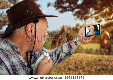 Telemedicine app lets a medical woman treat her rural patient remotely via video-chat. The old cowboy looks to the doc on the screen of his mobile phone. She shows how to check the pulse on the neck.  Royalty-Free Stock Photo #1845156343