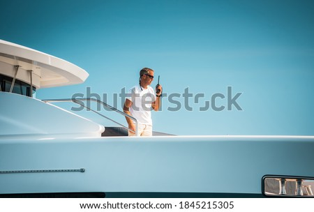Male superyacht Deckhand with a handheld radio getting ready to drop anchor, with a blue sky in the background Royalty-Free Stock Photo #1845215305