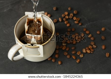 Pouring hot water into cup with drip coffee bag on black table, closeup Royalty-Free Stock Photo #1845224365