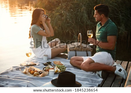 Woman taking picture of boyfriend on pier at picnic